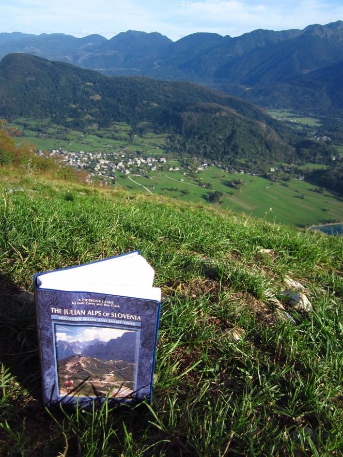 Kirjastosta lainaamani matkaoppaamme. Taustalla Stara Fužinan kylä.
